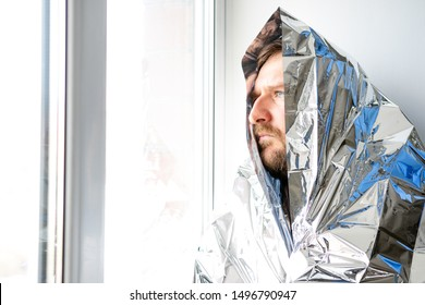 a man with a beard is wrapped in a large shiny material and looks out the window. blue eyes a look of alarm the danger of a radioactive attack
