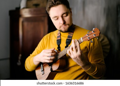 A man with a beard and a yellow sweater plays the ukulele. Male musician with ukulele posing for the camera