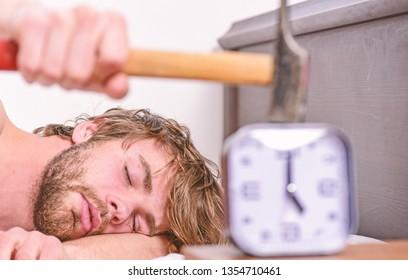 Man bearded annoyed sleepy face lay pillow near alarm clock. Guy knocking with hammer alarm clock ringing. Break discipline regime. Annoying sound. Stop ringing. Annoying ringing alarm clock.