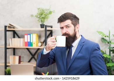 Man bearded businessman hold coffee cup stand office background. Start day with coffee. Successful people drink coffee. Drinking coffee relaxing break. Boss enjoying energy drink. Caffeine addicted.