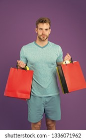 Man bearded face holds shopping bags. Guy bought lot sporty clothes and accessories. Man shopping on black friday. Guy bought lot items with discount. Seasonal sale concept. Do not miss sales.