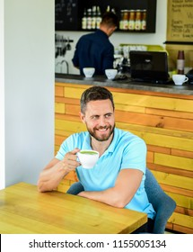 Man bearded guy drinks cappuccino wooden table cafe. Cafe visitor happy smiling face enjoy coffee drink. Improve overall health. Take moment to care about yourself. Coffee drinkers live longer.