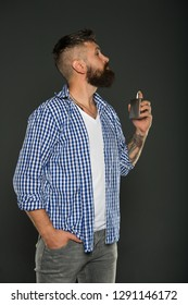 Man bearded handsome hold bottle perfume. Fragrance for brutal hipster. Fashion and beauty treatment. Masculine fragrance for brutal guy. Masculinity concept. Perfume male fragrance. Smell fragrance.