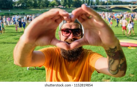 Man bearded hipster in front of crowd people show heart gesture riverside background. Hipster happy celebrate event picnic fest or festival. Urban event celebration. Cheerful fan love summer fest.