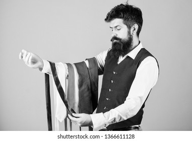Man bearded hipster hold few neckties. Guy with beard choosing necktie. Perfect necktie. Select tie that has colors of your suit and shirt as well as at least one other color to provide an accent.