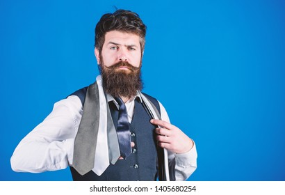 Man bearded hipster hold few neckties on blue background. Guy with beard choosing necktie. Gentlemens guide. How to choose right tie. Classic style. How to match necktie with shirt and suit.