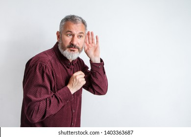 Man bearded hipster hold hand near ear to hear better, eavesdropping and spying, hearing test. Guy try to hear better with hand palm. Hipster with beard and mustache has hearing problems.
