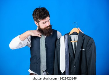 Man bearded hipster hold neckties and formal suit. Perfect necktie. Shopping concept. Stylist advice. Difficulty choosing necktie. Shop assistant or personal stylist service.Matching necktie outfit.