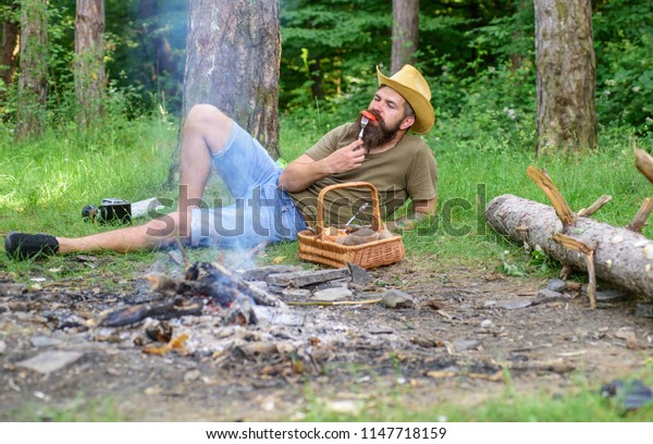 Man bearded hipster lay near campfire after day hiking or gathering mushrooms. Man have snack or picnic in forest. Guy relaxing near campfire and eating snacks. Brutal bearded tourist relaxing.