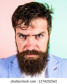 Man bearded hipster on strict face pink blue background. Hipster guy with messy tousled hair and long beard needs barber service. Keep hair tidy and care about hairstyle. Barber tips grooming beard.