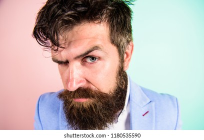 Man bearded hipster on strict face pink blue background. Barber tips grooming beard. Hipster guy with messy tousled hair and long beard needs barber service. Keep hair tidy and care about hairstyle.