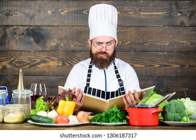Man bearded hipster read book recipe near table fresh vegetables. Culinary arts. Recipe to cook healthy food. Vegetarian recipe. Experienced chef cooking excellent dish. This recipe is just perfect.