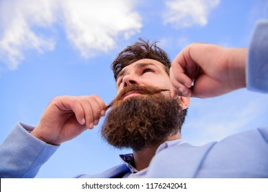 Man bearded hipster twisting mustache sky background. Ultimate moustache grooming guide. Hipster handsome attractive guy close up. Expert tips for growing and maintaining moustache.