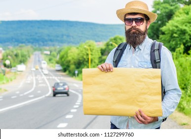 Man bearded hitchhiker stand at edge of road with blank paper sign, copy space. Benefits using sign with name destination. Cardboard sign with indication where you want go. Short general directions.