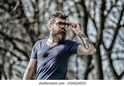 Man bearded with sunglasses nature background. Hipster confident in dark sunglasses. UV filter. Bearded hipster brutal man wear protective sunglasses. Bearded man wear modern fashionable sunglasses.