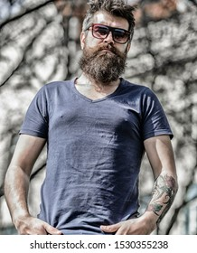 Man bearded with sunglasses nature background. Bearded man wear modern fashionable sunglasses. Hipster confident in dark sunglasses. UV filter. Bearded hipster brutal man wear protective sunglasses.