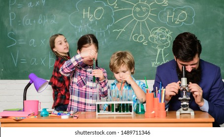 Man bearded teacher and pupils with test tubes in classroom. Observe reaction. Science is always the solution. School chemistry experiment. Explaining chemistry to kids. Fascinating chemistry lesson.