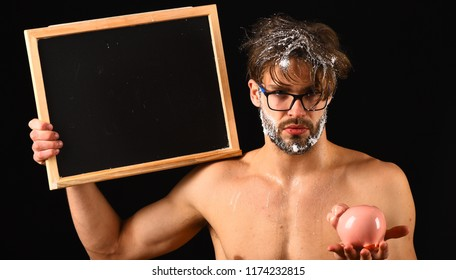 Man bearded tousled hair covered with foam hold piggy bank. Lack of water. Need take shower. Man naked body blackboard copy space. Macho attractive nude guy show blackboard. Expensive water tariff.