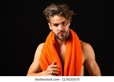 Man bearded tousled hair covered with foam or soap suds. Wash off foam carefully. Man with orange towel on neck ready to take shower. Body care concept. Macho attractive nude guy black background.