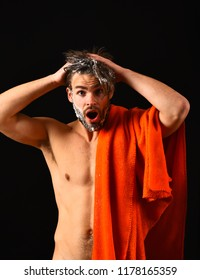 Man bearded tousled hair covered with foam or soap suds. Wash off foam with water carefully. Need take shower. Man with orange towel ready to take shower. Macho attractive nude guy black background.
