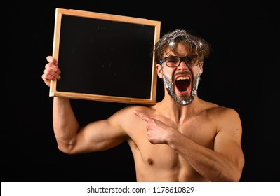 Man bearded tousled hair covered with foam wears eyeglasses. Lack of water. Need take shower. Man sexy muscular torso naked body hold blackboard copy space. Macho attractive nude guy show blackboard.