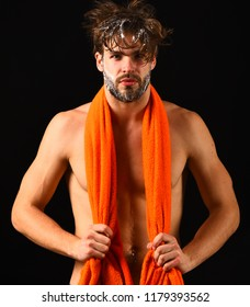 Man bearded tousled hair covered with foam or soap suds. Wash off foam with water carefully. Body care. Man with orange towel on neck ready to take shower. Macho attractive nude guy black background.