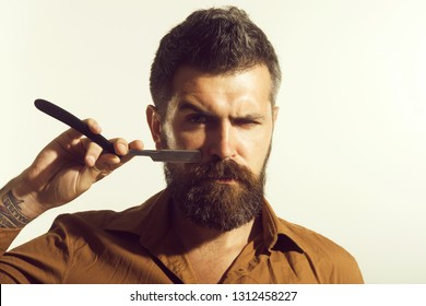 Man with beard&mustache holds straight razor. Hairdresser in stylish shirt demonstrate sharp blade dangerous razor. Bearded hairdresser with straight razor for shaving. Sexy macho with straight razor.