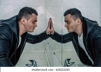 The man with the beaten person looks at the reflection. He in a black coat and a white t-shirt. The man thinks of something serious and as if looks to himself in soul.