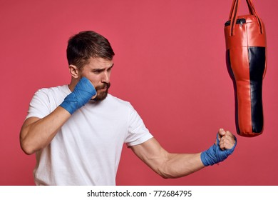 man beats a pear boxer on a light background, protection for hands, sports