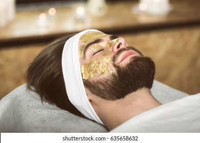 Man at beautician's during gold mask anti-aging therapy