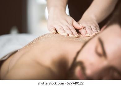 Un homme à l'esthéticienne reçoit un massage exfoliant avec épluchage de sel