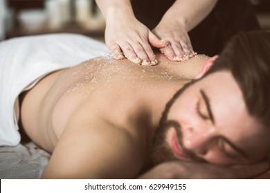 Der Mensch beim Kosmetiker erhält eine Peeling-Massage mit Salzschälen