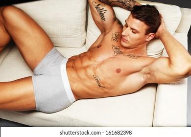 Man with beautiful muscular tattooed torso in underwear lying on sofa