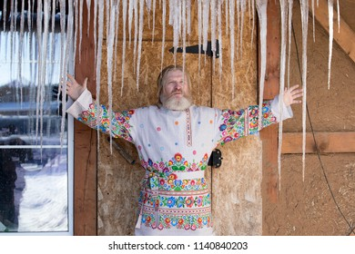 a man in a beautiful national painted shirt in the courtyard of the house looking at icicles in the spring