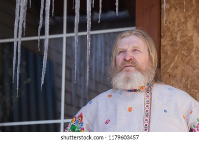 a man in a beautiful national painted shirt in the courtyard of the house looking at suckers in the spring