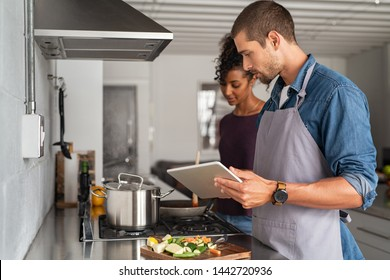 Man and beautiful woman preparing lunch while looking recipe from digital tablet. Young multiethnic couple using computer while cooking in kitchen at home. Husband and wife cooking pasta together.