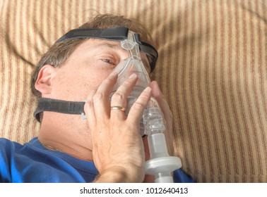 Man in bed adjusts CPAP mask