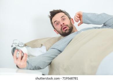 man in bed looking in shock at time on clock