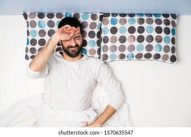 Man in bed in top view with tired and sick expression
