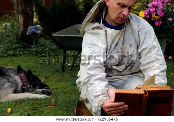 A man in beekeeper clothes reading a book, while his dog relaxing on the grass. Outdoor filtered photo