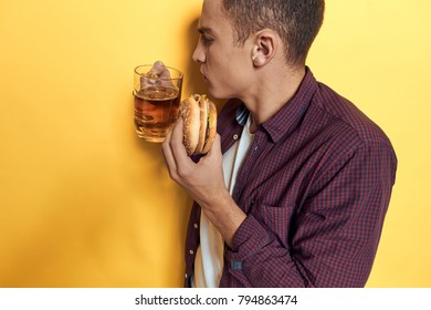 man with a beer and a hamburger on a yellow background