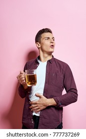man with beer holds his hand on his stomach, alcohol