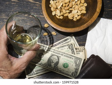 man with beer leaving tip on bar