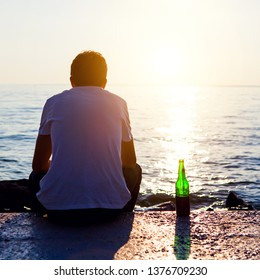 Man with a Beer sit at Seaside on Sunset Background
