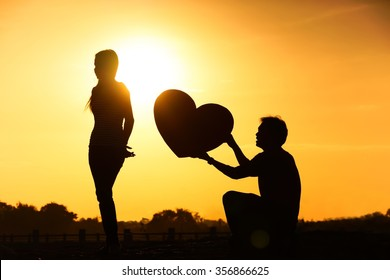 Man begging a woman for love by giving a big heart