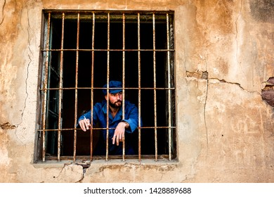 a man behind the bars in the prison