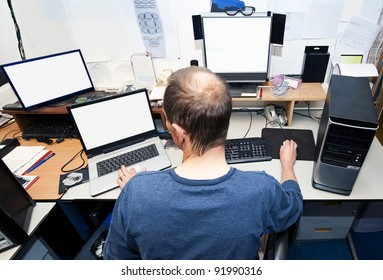 Man behind a desk with several computers and screens, repairing and installing new hardware
