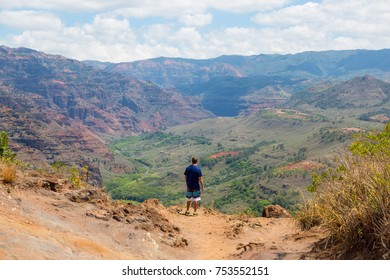 Man from behind dressed in sports gear standing in front of Waimea canyon on the island Kauai, Hawaii, USA