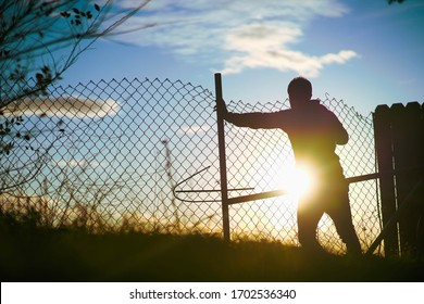 Man Behind Fence Overlooking Cliff At Sunset