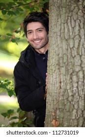 Man behind a tree trunk